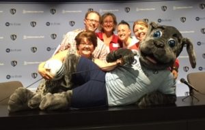 Look East team members pose with Blue, the Sporting KC mascot, during a scavenger hunt as part of a team-building exercise